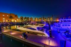 Porto Arabia Doha night yachts. Doha, Qatar - February 18, 2019:Luxurious yachts and boats at Porto Arabia Marina at night. The Pearl-Qatar in Doha artificial stock photography