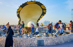 Pearl fountain in Doha, Qatar. DOHA, QATAR - FEBRUARY 13, 2018: People make selfies and watch the Pearl fountain, located on Corniche Promenade, on February 13 Royalty Free Stock Photos