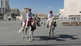 Police riding in Souq Waquif. Doha, Qatar - February 20, 2019: two heritage Police Officers in traditional 1940s Qatari uniform riding white Arabian Horses at stock video