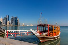 Doha, Qatar - Jan 8th 2018 - A orange traditional boat waiting for tourists to navigate in Doha`s downtown in a blue sky day. royalty free stock image