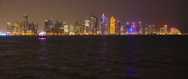 Doha skyllie with Emir image. DOHA, QATAR - NOVEMBER 11, 2017: Night view of the city`s towers during the diplomatic crisis, with huge pictures of the emir on Stock Image
