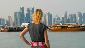 Doha seafront happy woman. Happy woman backside relaxing on seafront of Doha park along Doha Bay with traditional dhow. Lifestyle tourist at East Mound-Skyline stock video