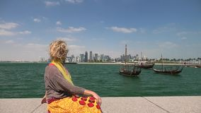Doha seafront happy woman. Happy woman on seafront of Doha park along Doha Bay with traditional dhow on background. Lifestyle caucasian tourist enjoys East Mound stock video footage