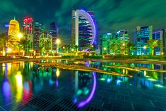 Doha skyline night. Doha West Bay high rises illuminated by night reflecting in downtown park. Colorful glassed skyscrapers of Doha skyline, Qatar, Middle East stock photo
