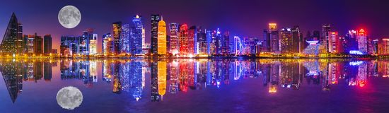 Doha skyline reflection night. Banner panorama of Doha West Bay skyline lighting by night reflecting in Doha Bay. Modern skyscrapers of Doha with full moon stock images