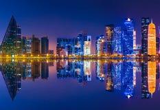 Doha skyline reflection night. Doha West Bay skyline lighting by night reflecting in Doha Bay. Modern skyscrapers of Doha in Qatar, Middle East, Arabian stock photo