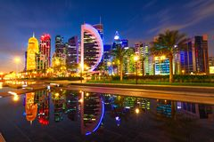 Doha skyline reflection night. Doha West Bay high rises illuminated by night reflecting in the water of park in Downtown. Modern skyscrapers of Doha skyline royalty free stock photo