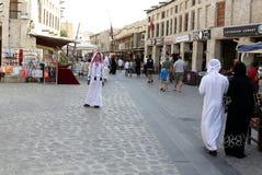Doha souq shoppers. DOHA, QATAR - APRIL 9, 2017: Shoppers in the main thoroughfare of Souq Waqif market in Qatar, Arabia Stock Photo
