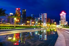 Doha West Bay night. Doha West Bay high rises at night reflecting in the water of downtown park. Lighting skyscrapers of Doha skyline in Qatar, Middle East royalty free stock images
