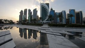 Doha West Bay reflection. Doha West Bay high rises at sunset light reflecting in the water of park in Downtown. Modern skyscrapers of Doha skyline in Qatar stock video footage