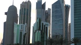 Doha West Bay reflection. Doha, Qatar - February 18, 2019: close up of Doha West Bay high rises at sunset in Sheraton Park downtown. Modern skyscrapers of Doha stock video