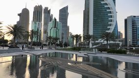 Doha West Bay reflection. Doha, Qatar - February 18, 2019:Scenary of Doha West Bay skyline at sunset reflecting in the water. Modern glassed skyscrapers of Doha stock video