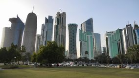 Doha West Bay skyline. Doha, Qatar - February 18, 2019:Doha West Bay high rises at sunset from green lawn along corchiche promenade. Modern skyscrapers of Doha stock footage