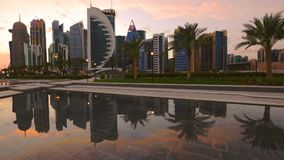 Doha West Bay skyline. Time lapse sunset to night: Doha West Bay skyline reflecting in the water of fountain. Modern glassed skyscrapers of Doha skyline in Qatar stock video