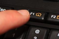 Doigt appuyant sur la touche de F1/Home photographie stock libre de droits