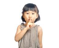 Doigt asiatique de petite fille jusqu'aux lèvres pour faire un geste tranquille i Images libres de droits