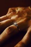 Doigt avec l'anneau de mariage Photos stock