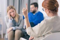 Doigt de l'apparence une de thérapeute tout en parlant à ses patients pendant une thérapie image stock