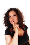 Doigt de petit morceau de femme au-dessus de bouche Photographie stock
