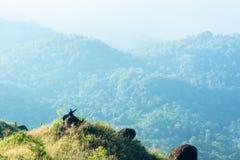 Doigt de séance et de point d'homme sur le dessus en pierre de la montagne chez Kanchanaburi photo stock