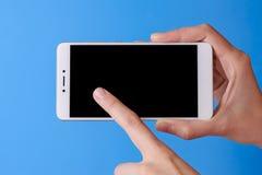 Doigt du ` s de femme touchant sur le mobile de téléphone avec l'affichage d'isolement sur le fond bleu photos libres de droits