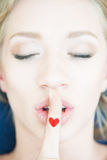 Doigt et coeur sur le visage Concept de silence, amour, baiser, va Photographie stock