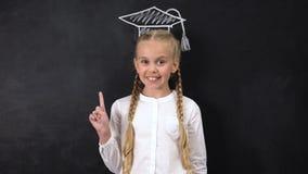 Doigt heureux de points d'écolière au chapeau scolaire peint sur le fond de tableau noir banque de vidéos