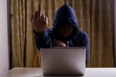 Doigt moyen d'exposition asiatique de pirate informatique tout en entaillant le réseau informatique Images libres de droits