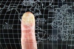 Doigt sur la carte du monde photos stock