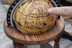 Doigt sur un globe Photographie stock
