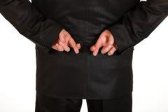 Doigts croisés par fixation d'homme d'affaires derrière en arrière. Image libre de droits
