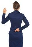 Doigts croisés par participation de femme d'affaires derrière de retour Photos stock