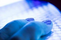 Doigts dans l'émetteur à rayonnement ultraviolet Photos libres de droits