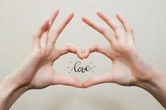 Doigts dans la forme de coeur Amour à l'intérieur d'éclat de mains Photos stock