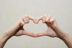 Doigts dans la forme de coeur Amour à l'intérieur d'éclat de mains Images stock