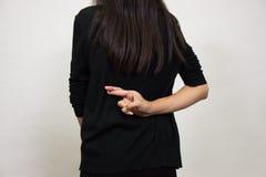 Doigts de femme croisés sur le sien de retour Image stock