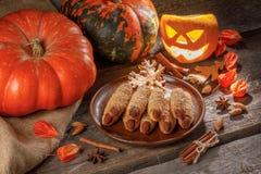 Doigts de sorcière de biscuit sur une table en bois entourée par des potirons photo libre de droits