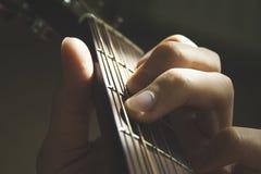 Doigts des mains de l'homme sur les ficelles de guitare acoustique étroites vers le haut du macro tir sur l'éclat du soleil Musiq photos stock