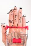 Doigts drôles faisant des emplettes au supermarché avec le chariot rouge à chariot sur le fond blanc Photos libres de droits
