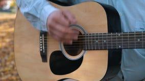 Doigts en gros plan d'un homme jouant la guitare acoustique dehors banque de vidéos