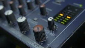 Doigts femelles tournant le bouton d'affaiblisseur sur le mélangeur audio clips vidéos