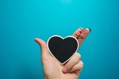 Doigts heureux peints souriants dans l'amour avec le coeur de tableau noir Photographie stock libre de droits
