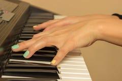 Doigts jouant les claviers de piano électroniques Photos stock