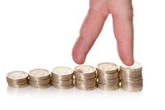 Doigts marchant sur des piles de pièces de monnaie d'une livre Image stock