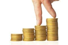 Doigts marchant vers le bas sur des piles de pièces de monnaie Photos stock