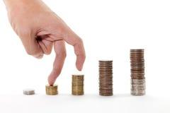 Doigts marchant vers le haut sur des piles de pièces de monnaie sur le fond blanc Photo libre de droits