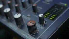 Doigts masculins tournant le bouton d'affaiblisseur sur le mélangeur audio banque de vidéos