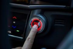 Doigts pressant le bouton marche de voiture Images libres de droits