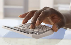 Doigts pressant sur le clavier numérique de calculatrice Photo stock