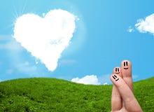 Doigts souriants heureux regardant le nuage en forme de coeur Images stock